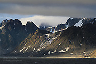 Mountains soar from sea to clouds in Smeerenburgfjorden on the north coast of Spitsbergen island; Svalbard, Norway.