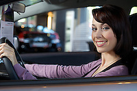 Portrait of young woman sitting in driver's seat at car dealership