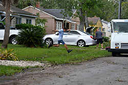 USPS letter carrier jumps over standing water as residents in the Southside neighborhood of Jacksonville, FL returns on September 12, 2017 after Hurricane Irma.<br /> Flood water of the storm surge damaged many homes in the neighborhood after the storm system took an unexpected turn and caused massive power outages and coastal flooding around the state.