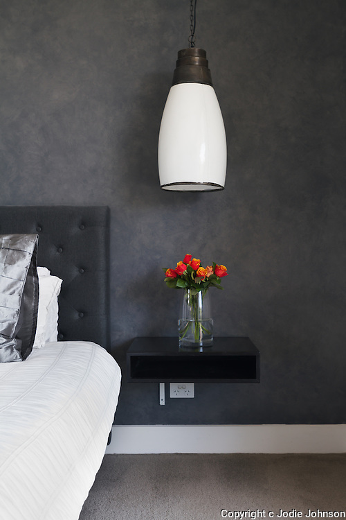Orange roses on bedside table in contemporary dark bedroom design with pendant lighting