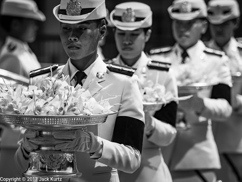 26 OCTOBER 2017 - BANGKOK, THAILAND:  Women hold sandalwood flowers for people to leave as offerings during the funeral ceremony for Bhumibol Adulyadej, the Late King of Thailand. The king died on 13 October 2016 and was cremated 26 October 2017, after a mourning period of just over one year. The revered monarch was the longest reigning king in Thai history and is credited with guiding Thailand through the turbulent latter half of the 20th century.    PHOTO BY JACK KURTZ