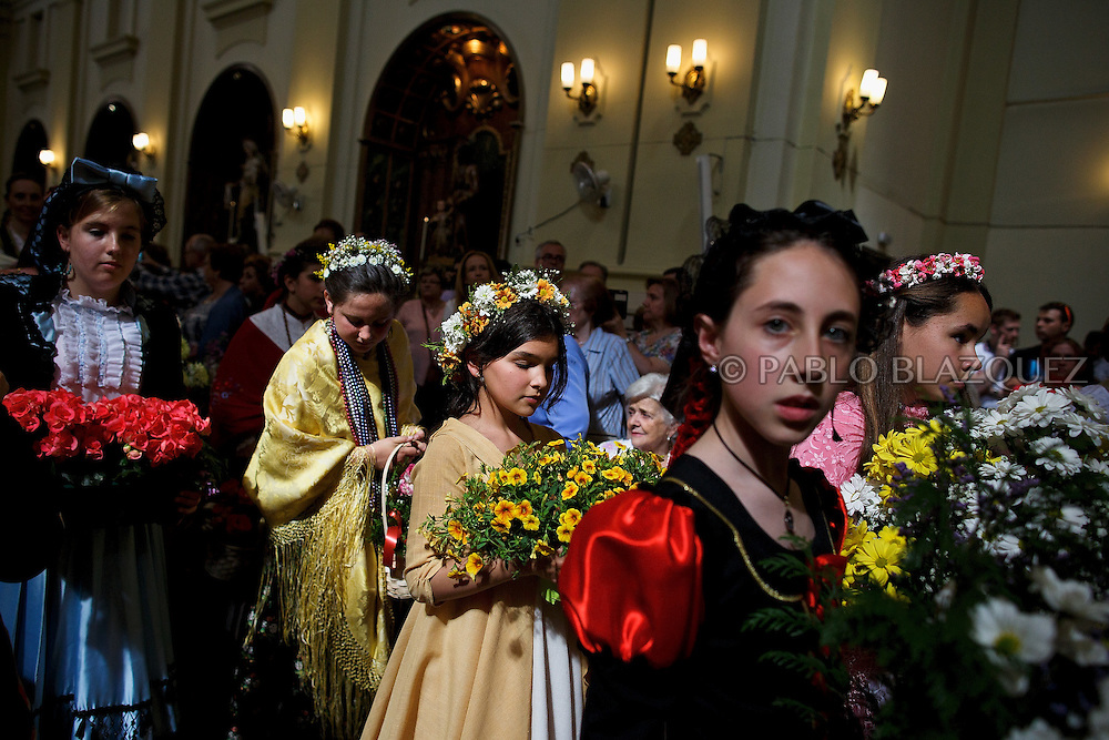 'Mayas' stand inside the San Lorenzo Church as they cerebrate the 'La Maya' tradition on May 10, 2015 in Lavapies neighborhood, Madrid, Spain. 'La Maya' festivity is a pagan tradition to celebrate the beginning of the spring which is believed to come from the medieval age. In old times the 'Maya's Festival' used to take place at The 'Mayas' field' (Prado de las Mayas) which is where now the San Lorenzo church is located. La Maya combines symbols of fertility and prosperity on agriculture and shepherding economy. A 'Maya' girl dressed with traditional customs sits on an altar in the street decorated with flowers, plants and cushions. Other Mayas and Mayos offer flowers, traditional sweets, lemonade, and wine to members of the public as they play music and dance. (© Pablo Blazquez)