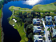 Aerial view of Weston Hills Country Club, Weston, Florida.  Green and fairway with homes on course.  Pennsular on lake