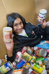 United States, Washington, Seattle, girl (age 9) with cans of food at food bank.  MR