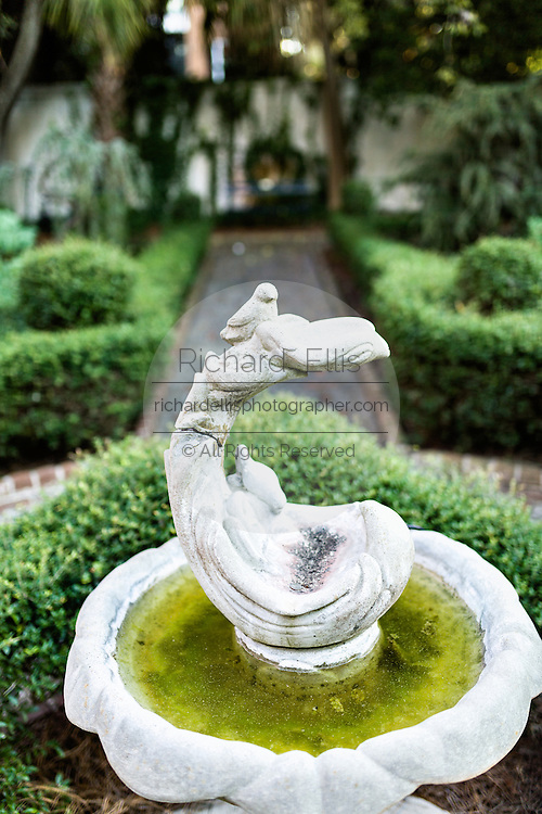 Fountain in the Philip Simmons Gardens at St John's Reformed Episcopal Church designed by topiary artist Pearl Fryar in historic Charleston, SC.