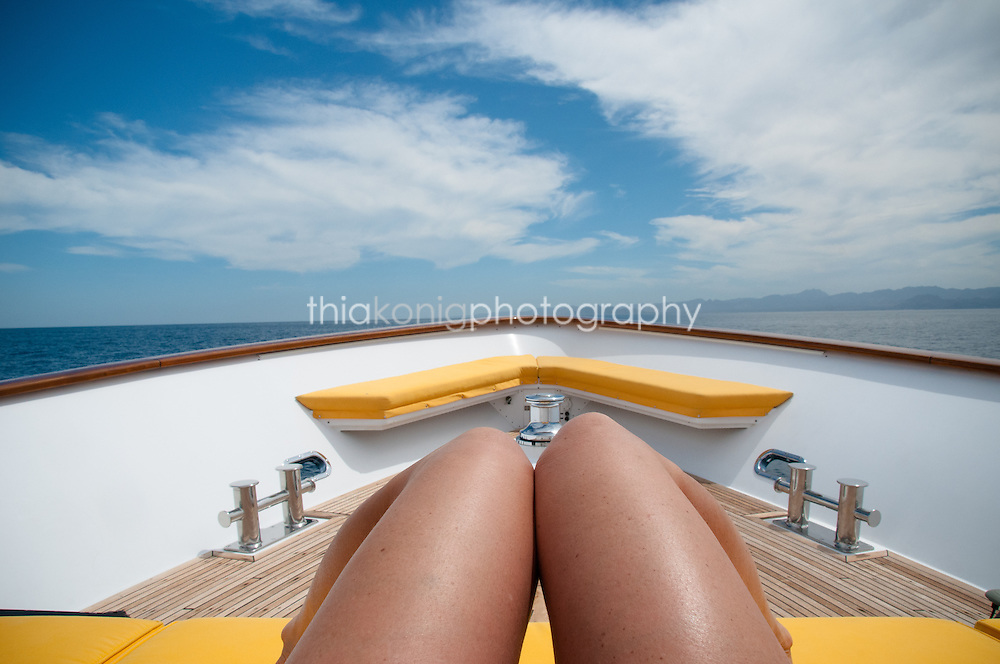 View down woman's thighs to bow of yacht with yellow cushions, Sea of Cortez, Mexico.