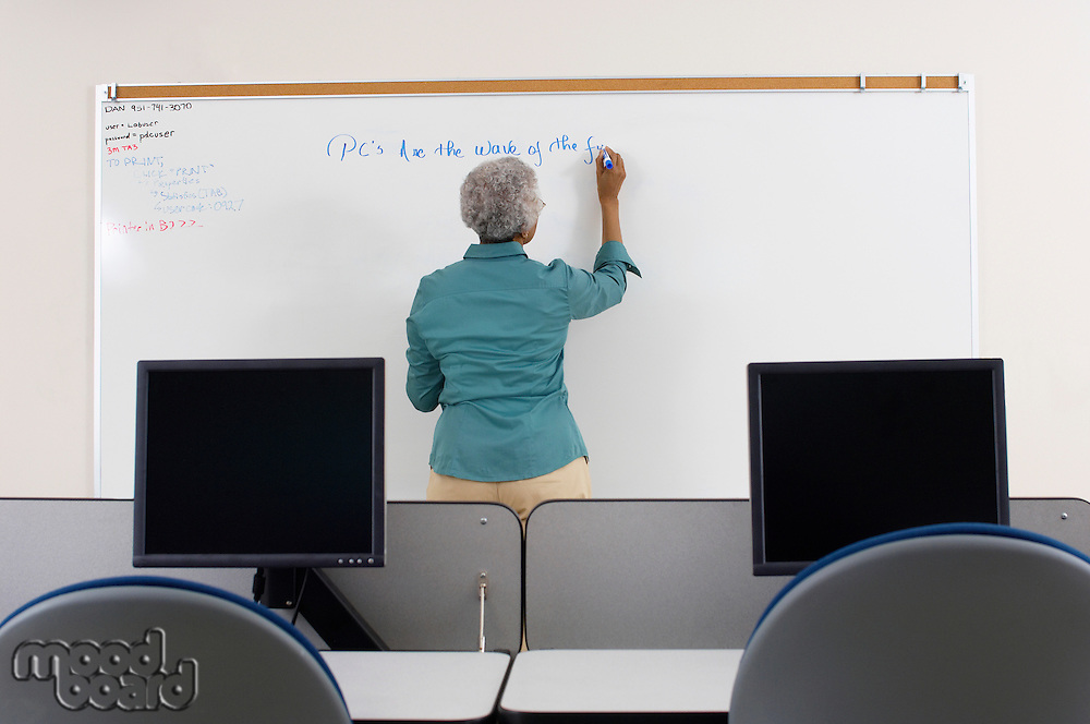 Female teacher writing on whiteboard in computer classroom