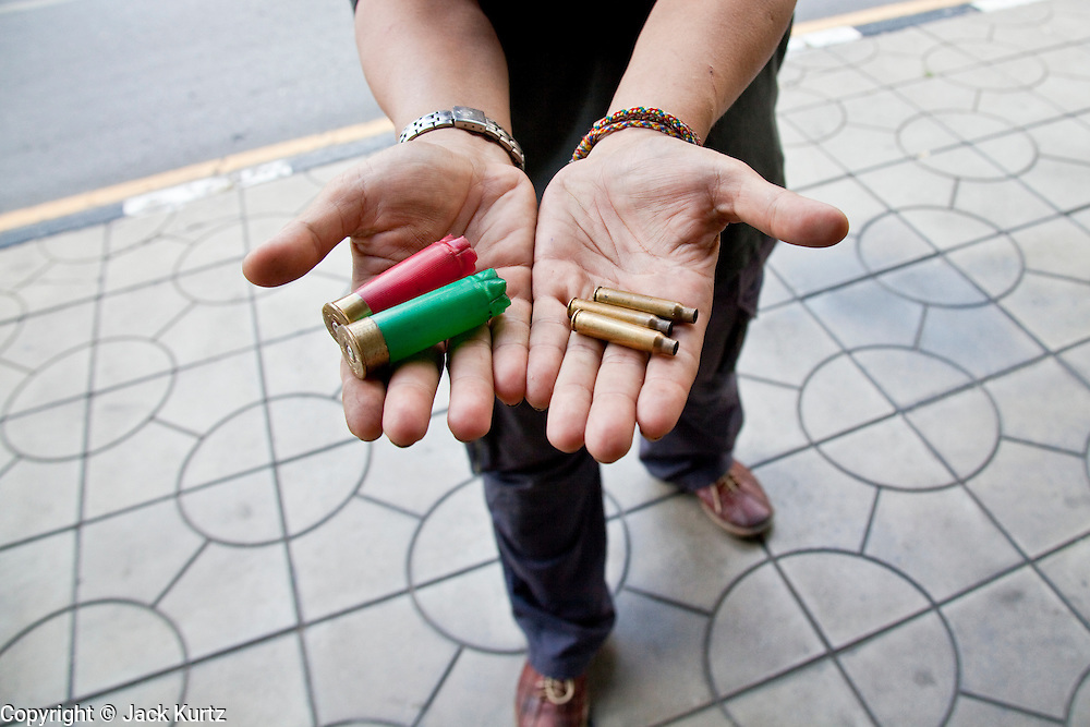14 MAY 2010 - BANGKOK, THAILAND: A Red Shirt protester shows off spent shell casings he says were fired by the Thai Army towards Red Shirt positions at the intersection of Rama IV and Witthayu Roads in Bangkok Friday morning. Tensions among Red Shirt protesters demanding the dissolution of the current Thai government rose overnight after Seh Daeng, the Red Shirt's unofficial military leader was shot in the head by a sniper. Gangs of Red Shirts have taken over military checkpoints on Rama IV and are firing small rockets at military helicopters and army patrols in the area. Troops have responded by firing towards posters.  PHOTO BY JACK KURTZ