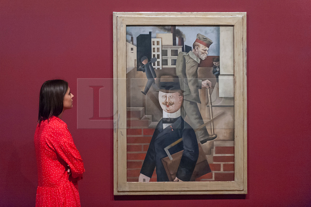 """© Licensed to London News Pictures. 04/06/2018. LONDON, UK. A gallery staff member views """"Grey Day, Grauer Tag"""", 1921, by George Grosz at a preview of """"Aftermath:  Art in the wake of World War One"""" at Tate Britain.  The exhibition marks 100 years since the end of the First World War, exploring the impact of the conflict on British, German, and French art in over 150 works from 1916 to 1932.  The show runs 5 June to 23 September 2018.  Photo credit: Stephen Chung/LNP"""