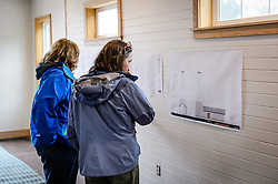 Haines resident Jennifer Allen (right, woman left is unidentified) look at architectural blueprints as they tour the recently restored fire hall located on the grounds of historic Fort William H. Seward in Haines, Alaska during an open house to celebrate the completion of the restoration.<br /> <br /> After being absent from the historic Fort Seward skyline since approximately the 1930s, the 60-foot tower of the fort&rsquo;s fire hall has been restored to its original height. The building and tower, built around 1904 in Haines, Alaska, was shortened to approximately half its height in the 1930s for unknown reasons. The restoration included rebuilding a missing 35-foot section of the 60-foot tower whose purpose was to dry fire hoses. The tower restoration was completed by building its four sections on the ground and then hoisting those sections with a crane into place on top of each other.<br /> <br /> Through the years, the historic Fort Seward area, a former U.S. Army post, has been referred to as Fort William H. Seward, Chilkoot Barracks, and Port Chilkoot. The National Historic Landmarks listing record for the fort says that &quot;Fort Seward was the last of 11 military posts established in Alaska during the territory's gold rushes between 1897 and 1904. Founded for the purpose of preserving law and order among the gold seekers, the fort also provided a U.S. military presence in Alaska during boundary disputes with Canada. The only active military post in Alaska between 1925 and 1940, the fort was closed at the end of World War II.&rdquo; <br /> <br /> The bottom portion of the fire hall is being leased as commercial space. Due to fire code restrictions there is no public access to the upper portion of the tower. <br /> <br /> The fire hall was restored over a two-year period by owners Joanne Waterman and Phyllis Sage who also own the fort&rsquo;s original guardhouse located next door to the fire hall. That building, now known as the Alaska Guardhouse, is a bed and breakfast.