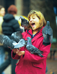BUENOS AIRES, ARGENTINA:  A woman stands with pigeons in Buenos Aires, Argentina. .(Photo by Ami Vitale)