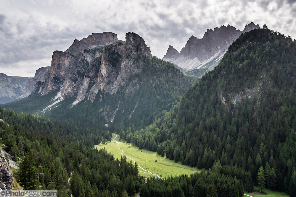 A short ascent to Wolkenstein Castle gives a good view over Vallunga/Langental valley, in Puez-Geisler Nature Park, Val Gardena, Dolomites, South Tyrol, Italy, Europe. The beautiful ski resort of Selva di Val Gardena (German: Wolkenstein in Gröden; Ladin: Sëlva Gherdëine) makes a great hiking base in the Dolomites, in the South Tyrol region (Trentino-Alto Adige/Südtirol) of Italy, Europe. For our favorite hike in the Dolomiti, start from Selva with the first morning bus to Ortisei, take the Seceda lift, admire great views up at the cross on the edge of Val di Funes (Villnöss), then walk 12 miles (2000 feet up, 5000 feet down) via the steep pass Furcela Forces De Sieles (Forcella Forces de Sielles) to beautiful Vallunga (trail #2 to 16), finishing where you started in Selva. The hike traverses the Geisler/Odle and Puez Groups from verdant pastures to alpine wonders, all preserved in a vast Nature Park: Parco Naturale Puez-Odle (German: Naturpark Puez-Geisler; Ladin: Parch Natural Pöz-Odles). UNESCO honored the Dolomites as a natural World Heritage Site in 2009.