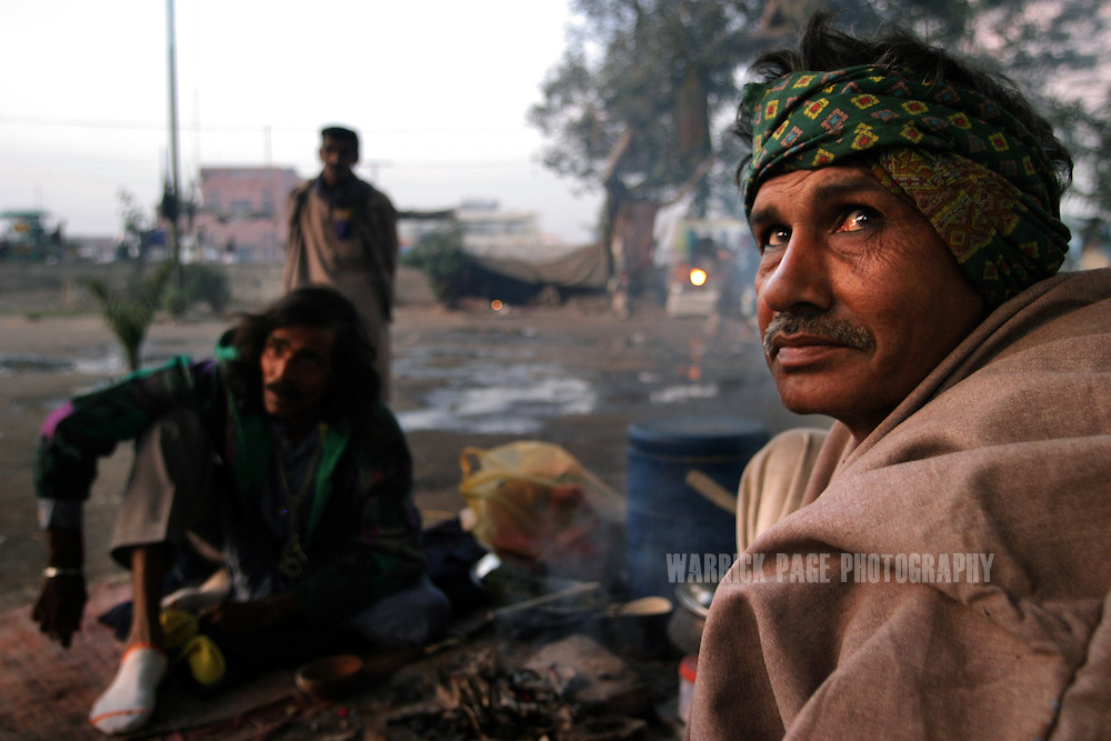 A heroin users gather around a small fire to keep warm at dusk, December 10, 2004, Lahore, Pakistan. Heroin is cheap and readily available in Pakistan due to it's proximity to Afghanistan which supplies almost 90% of heroin to Europe. Almost 20% of heroin produced in Afghanistan is trafficked through Pakistan according to the UN Office on Drugs and Crime (UNODC). With the fall of the Taliban, opium cultivation has risen dramatically in spite of Afghan and coalition forces attempts to stem production. Pakistan has between 3.5-4 million heroin users, one of the highest numbers of heroin users in the world, next to Iran. (Photo by Warrick Page)