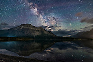 The Milky Way reflected in the unusually calm waters of Middle Waterton Lake from Driftwood Beach, in Waterton Lakes National Park, Alberta, Canada. The Park is an International Dark Sky Preserve, along with Glacier National Park in the U.S. The Park is also a U.N. World Heritage Site. <br /> <br /> Sagittarius, with Saturn and the Dark Horse dark nebula area is at centre; Scorpius and Antares are at right. <br /> <br /> This was June 17/18, 2018, on a windless night and a clear night between storm systems. <br /> <br /> This is a stack of 5 exposures for the ground, mean combined to smooth noise, and a single exposure for the sky and reflected stars, to minimize trailing. All were 25 seconds at f/2.2 with the Sigma 20mm Art lens and Nikon D750 at ISO 3200. Softening &ldquo;Orton&rdquo; style effects added to the sky and ground using Luminar and ON1 Photo RAW as filters.