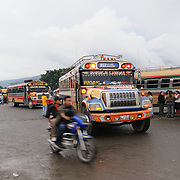 Chicken buses and a motorbike behind the Mercado Municipal (town market) in Antigua, Guatemala. From this extensive central bus interchange the routes radiate out across Guatemala. Often brightly painted, the chicken buses are retrofitted American school buses and provide a cheap mode of transport throughout the country.
