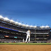 Derek Jeter, New York Yankees, heads out onto the field at the top of the fifth inning during the New York Yankees Vs Cincinnati Reds baseball game at Yankee Stadium, The Bronx, New York. 18th July 2014. Photo Tim Clayton