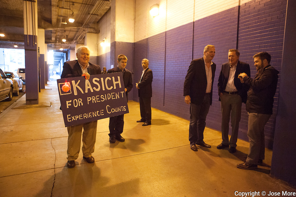Arthur Siml (CQ) carries a Kasich for president sign to the rally as Governor Kasich, right center, talk with supporters outside the Billy Goat Tavern. Ohio Governor and Republican presidential candidate John Kasich speaks during a short campaign stop at the Billy Goat Tavern in Chicago on Nov. 9, 2015.  <br /> Photography by Jose More