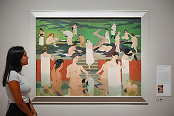 "© Licensed to London News Pictures. 27/06/2019. LONDON, UK.  A staff member views ""Bathing on a Summer Evening (Le Bain au soir d'été)"", 1892-93, by Félix Vallotton. Preview of ""Félix Vallotton:  Painter of Disquiet"", an exhibition of paintings and prints Swiss artist Félix Vallotton at the Royal Academy of Arts.  Around 100 works are on show 30 June to 29 September 2019.  Photo credit: Stephen Chung/LNP"