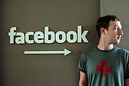 Mark Zuckerberg, Co-founder and CEO of Facebook, stands in front of a Facebook  sign in the downtown Palo Alto office Thursday, August 17, 2006. ..Photo by Erin Lubin For the Chronicle