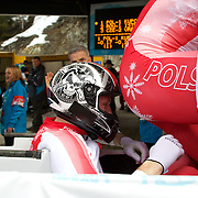 "Winter Olympics, Vancouver, 2010.The Polish team at the finish of the competition during the Bobsleigh Four-man at The Whistler Sliding Centre, Whistler, during the Vancouver Winter Olympics. 27th February 2010. Photo Tim Clayton..'BOB'..Images from the Four-man Bobsleigh Competition. Winter Olympics, Vancouver 2010..History was made at the Whistler Sliding Centre when the USA four-man bobsleigh team, led by Steven Holcomb took the Gold. The first time since 1948, a gap of 62 years, since the USA have won an Olympic Bobsleigh gold and they did it with their sleigh named ""Night Train""...The four days of practice and competition show the tension, nervousness and preparation as the teams of hardened men cope with the challenge of traveling at average speeds of over 150 km an hour. Indeed, five teams had already pulled out of the event before the opening heats because of track complexity, speed and fear, and on the final day, another four teams did not start after six crashes in the first two heats...Teams warm up behind the start complex, warming muscles in the cold in preparation for the explosive start. Many teams prepare in silence, mentally preparing themselves as they wait at the top of the run, in the bobsleigh sheds and the loading areas for their turn. When it's time to slide each team performs it's own starting ritual, followed by the much practiced start out of the blocks for just over four seconds, the teams are then in the hands of the accomplished drivers as they hurtle down the track for just over fifty seconds...Spectators clamber for the best position on track to see the sleighs for a split second, many unsuccessfully try to capture the moments on camera, The rumble of the sleigh is heard then the crowds gasp as it hurtles past in a blur...The American foursome of  Steven Holcomb, Justin Olsen, Steve Mesler and Curtis Tomasevicz finished with a pooled four-heat time of 3min 24.46sec. The German team led by Andre Lange won the Silver Medal in a combined"