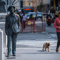 A woman with a dog walks past James Joyce's statue on the literary trail on the Gran Canale in Trieste, Italy