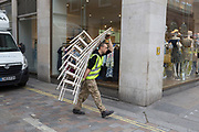 A workman delivers a tall stack of event chairs on 4th May 2017, in London, England.