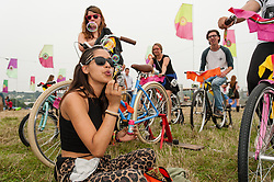 © Licensed to London News Pictures. 05/09/2014. Isle of Wight, UK. Festival goers at Bestival 2014 Day 2 Friday exercising on cycle machines, and a girl blows soap bubbles, while dance music plays loudly as an invigorating start to the day for a weekend of live music.  This weekend's headliners include Chic featuring Nile Rodgers, Foals and Outcast Photo credit : Richard Isaac/LNP