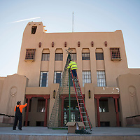 City of Gallup Parks and Recreation workers Matthew Retan (left), and Odie Garcia (on ladder) putting  Christmas decorations up in the McKinley County Courthouse Square, Monday Nov. 19 in Gallup.