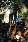 One of the protesters outside the court house in Jena stands under an old live oak while hoolding a poster of a noose during the ralley.Thousands gather outsied the La Salle parish court house to show their support for the Jena 6 Thursday Sept. 20,2007.(Photo/SuziAltman)