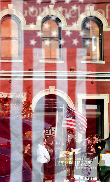 Photo by Gary Cosby Jr.     The float from the Disabled American Veterans Chapter 11 is reflected in a store front window on Bank Stree that is displaying and American Flag during the Veteran's Day Parade in Decatur.