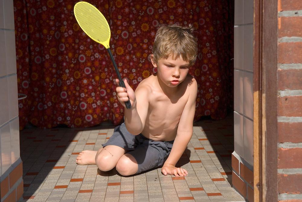 Ein Junge versucht Fliegen mit Hilfe einer Fliegenklatsche zu toeten   |  boy kills flies  with a fly flap  |