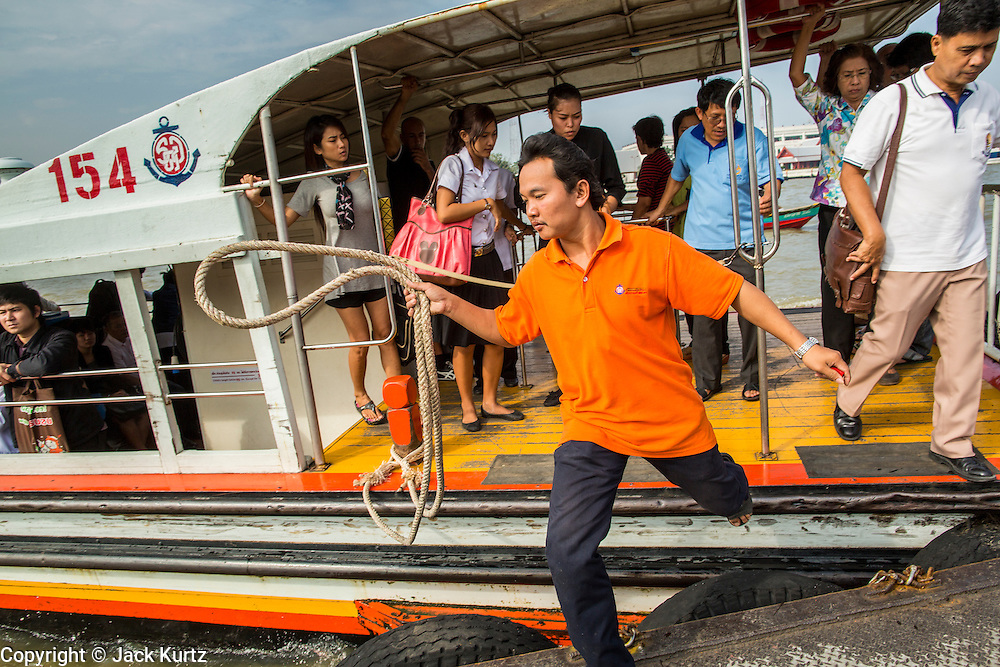 21 NOVEMBER 2012 - BANGKOK, THAILAND:  A crewman jumps off a still moving Chao Phraya Express Boat to tie it to the pier so passengers can embark and disembark. The Chao Phraya Express boats run up and down the Chao Phraya River in Bangkok providing a sort of bus service for neighborhoods near the river. The boats are the fastest way to get from north to south in Bangkok. Thousands of people commute to work daily on the Chao Phraya Express Boats and fast boats that ply Khlong Saen Saeb. Boats are used to haul commodities through the city to deep water ports for export.   PHOTO BY JACK KURTZ