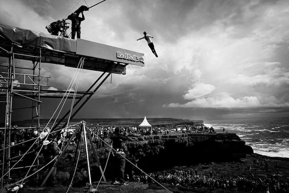 Colombian high diver, Orlando Duque, leaps from the board high above the 'Serpent's Lair' on Inis Mor, Ireland. Red Bull Cliff Diving World Series 2012. 03 August 2012