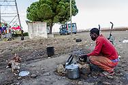 Boreano, Basilicata, Italia, 13/09/2013 <br /> Un ragazzo prepara qualcosa da mangiare, dopo una giornata di lavoro nei campi di pomodoro <br /> <br /> Boreano, Basilicata, Italy, 13/09/2013 <br /> A guy cooking something after a long day of work on tomato lands