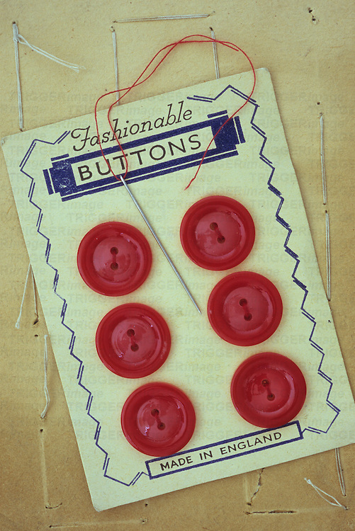 Six red dress or blouse or cardigan buttons attached to display card lying on card with sewing needle and red cotton thread