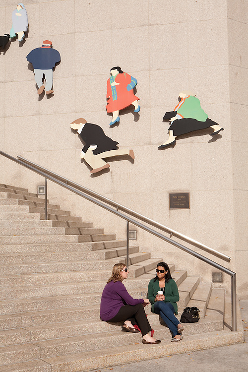 "Two women relaxing near the Royal Bank of Canada, by a public sculpture by Catherine Widgery entitled ""City People""."
