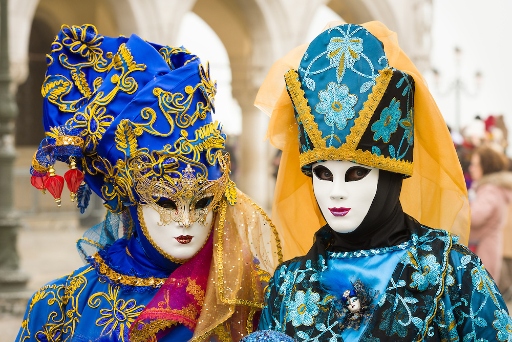 A woman isTwo women are seen Mark's Square wearing traditional Volto masks during the 2017 Venice Carnival