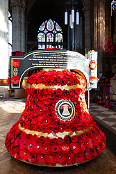 © Licensed to London News Pictures. 9/10/2018. Warwick, UK. Poppy display. Sixty two thousand, four hundred and thirty eight poppies have been assembled in St Mary's  church Warwick to commemorate the ending of the first World War. The poppies have been produced by local people, groups and school children with six hundred and ten alone covering the bell near the altar. As well as red poppies there are differing colours to signify conscious objectors, animals and pigeons killed in the Great War. Pictured, the bell decorated with 610 poppies. Photo credit: Dave Warren/LNP