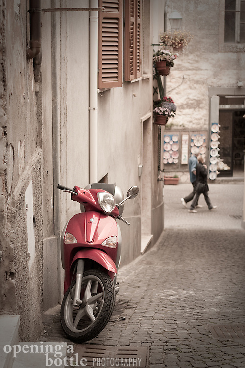 A red moped — aka motorino — parked on a street scene, Orvieto, Umbria, Italy. Full-color version available upon request.
