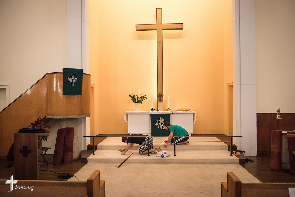 Asylum seekers clean the carpet next to the altar following Bible study on Saturday, Nov. 14, 2015, at the Dreieinigkeits-Gemeinde, a SELK Lutheran church in Berlin-Steglitz, Germany.  LCMS Communications/Erik M. Lunsford