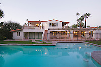 Swimming pool and lit exterior of Palm Springs home exterior