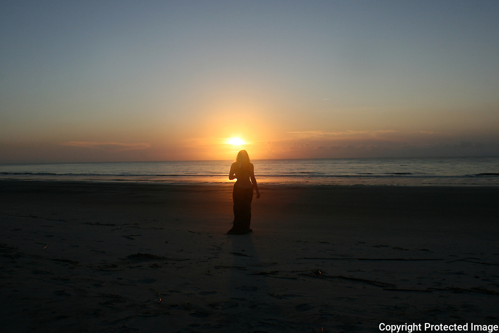 red head woman walking into the sunrise on Jekyll Island beach