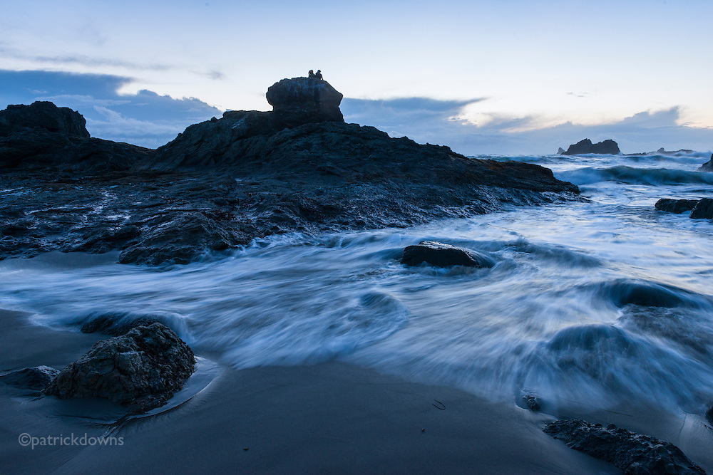 A couple enjoys their high perch on seaside rocks, as the incoming tide surges around them at deep dusk. Brookings, Oregon.