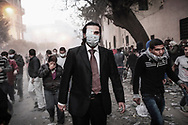 A protester wearing tie and suit runs away from the tear gas cloud on Mohamed Mahmoud street near Tahrir Square during stand off and clashes with riot police on November 22, 2011 in Cairo, Egypt.