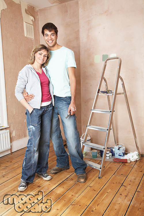 Couple embracing in unrenovated living room