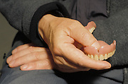 older man holding his artificial teeth