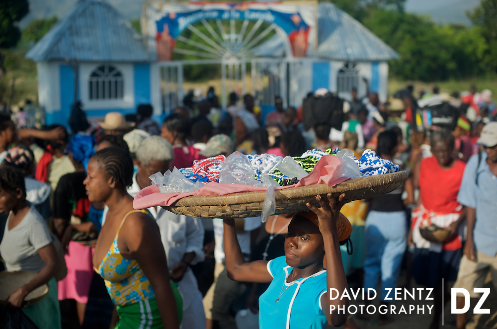 A woman sells colorful beads designed to appeal to different spirits outside the crowded entrance to the voodoo festival at Saut D'eau in central Haiti. The local government has erected a gate and begun charging an entrance fee to the festival. Despite being small, it is apparently enough to have deterred some of the more rural pilgrims, who cannot afford the fee.