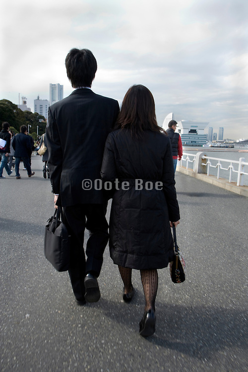 young adult Japanese business man and woman couple walking together