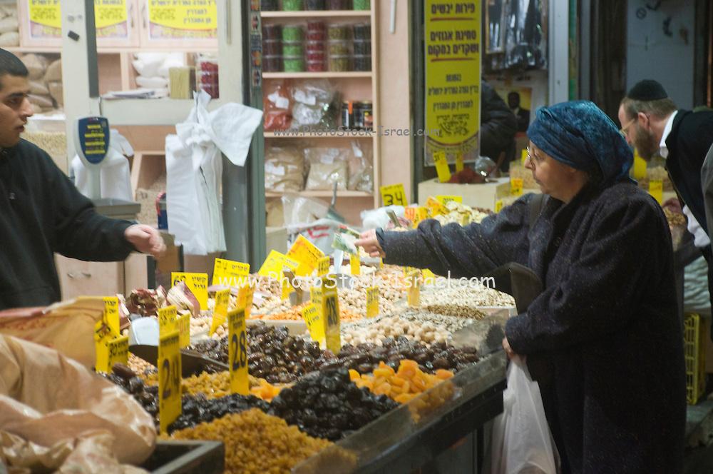 Israel, Jerusalem, Machane Yehuda market at night. Mature woman paying for dried fruit she has bought