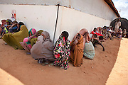 Refugees sit lined up in the shade at the Dagahaley refugee camp in Dadaab, Kenya, August 8, 2011. (Official White House Photo by David Lienemann)